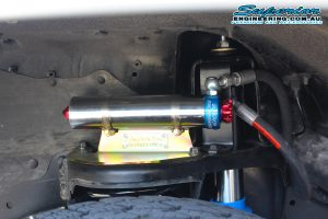 Closeup view of a single Superior remote reservoir and res mount fitted to the coil tower of a Nissan Patrol on the hoist at the Deception Bay 4x4 fitting workshop