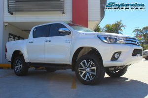 Front right view of a brand new white Toyota Hilux Revo (dual cab) after being fitted with a 2 inch Bilstein lift kit at the Superior Engineering Deception Bay 4WD Retail Store