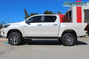 Left side view of a brand new white Toyota Hilux Revo (dual cab) fitted with a 2 inch Bilstein lift kit at the Superior Engineering Deception Bay 4WD Retail Store