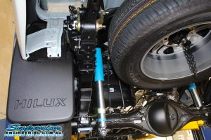Closeup view of a set of Bilstein shocks, leaf springs and shackles fitted to the rear of a new Toyota Hilux Revo four wheel drive
