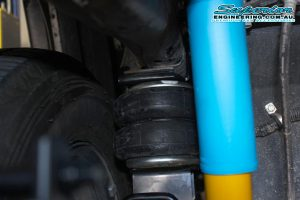 Closeup view of a single Airbag Man heavy duty Firestone leaf spring airbag fitted to the chassis and leaf spring on the single cab Toyota Hilux Revo