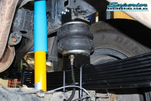 Closeup view of a single Airbag Man heavy duty Firestone airbag and mounting brackets and air hoses fitted to the chassis and leaf spring on the single cab Toyota Hilux Revo