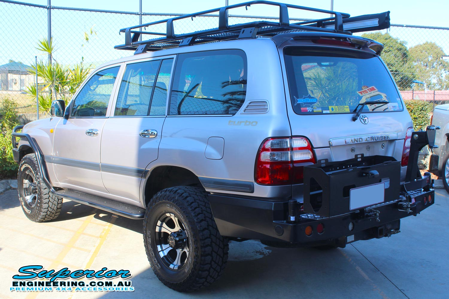 Left rear end view of a silver 100 Series Toyota Landcruiser fitted with an MCC4x4 Rear Bar with Wheel Carrier and Dual Jerry Can Holder