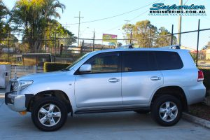 Left side view of a silver 200 Series Toyota Landcruiser wagon fitted with a premium 2 inch Superior Adjustable Remote Reservoir Lift Kit in the car park at the Deception Bay 4wd retail showroom