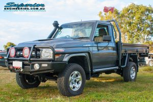 Front left view of a grey single cab 79 Series Toyota Landcruiser fitted with a full coil conversion kit and rear track width correction system at Superiors Burpengary workshop