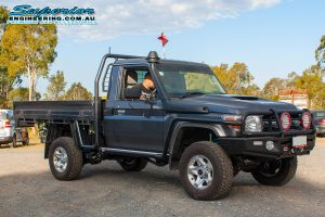 Front right view of a grey single cab 79 Series Toyota Landcruiser fitted with a full coil conversion kit and rear track width correction system at Superiors Burpengary workshop