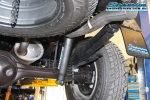 Closeup view of a single Ironman leaf spring and foam cell pro shock fitted to the rear end of a dual cab Isuzu D-Max at the Superior Engineering 4wd workshop and hoist