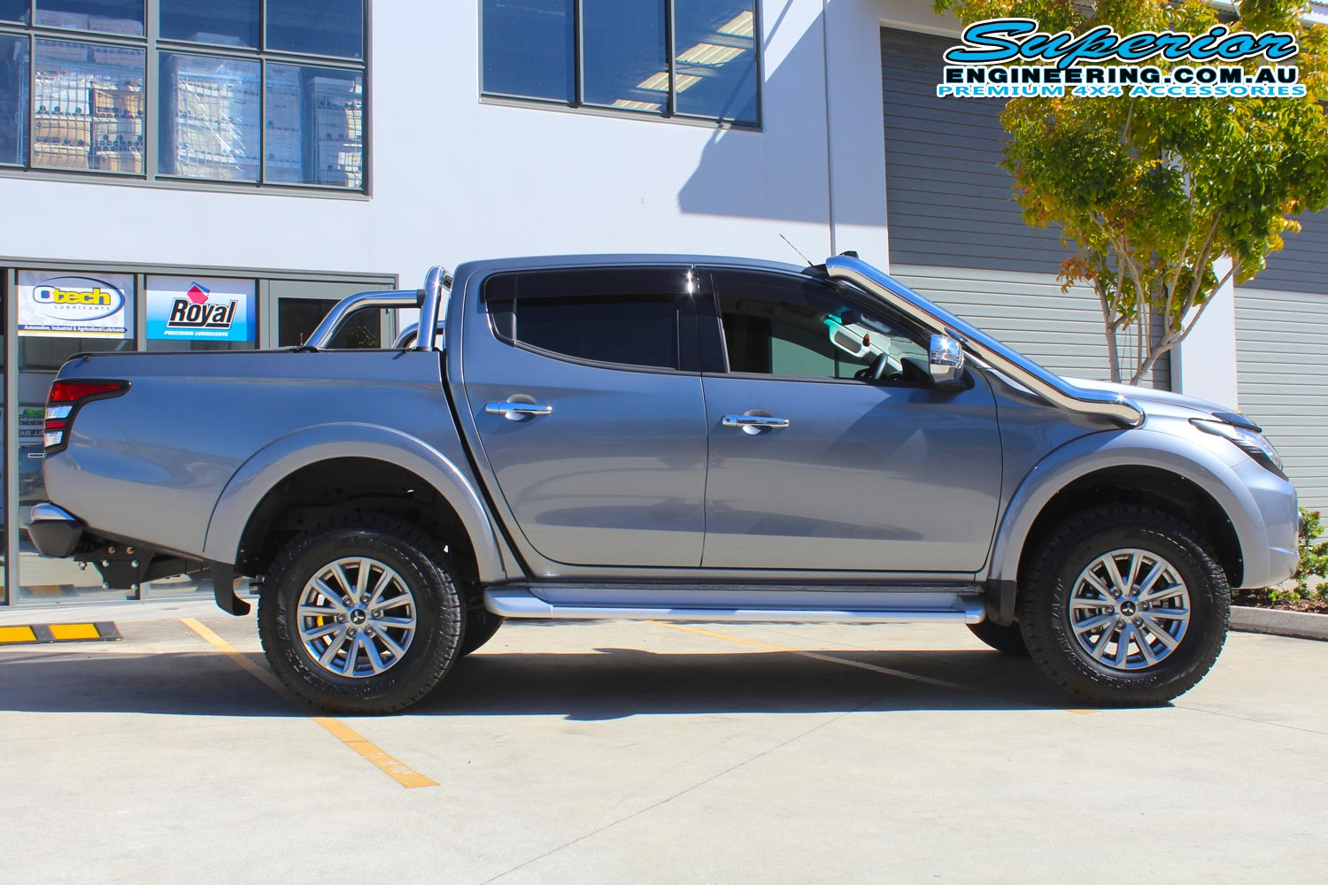 Right side view of a grey MQ Mitsubishi Triton four wheel drive after being fitted with a 40mm Bilstein lift kit at the Superior Engineering 4x4 retail showroom