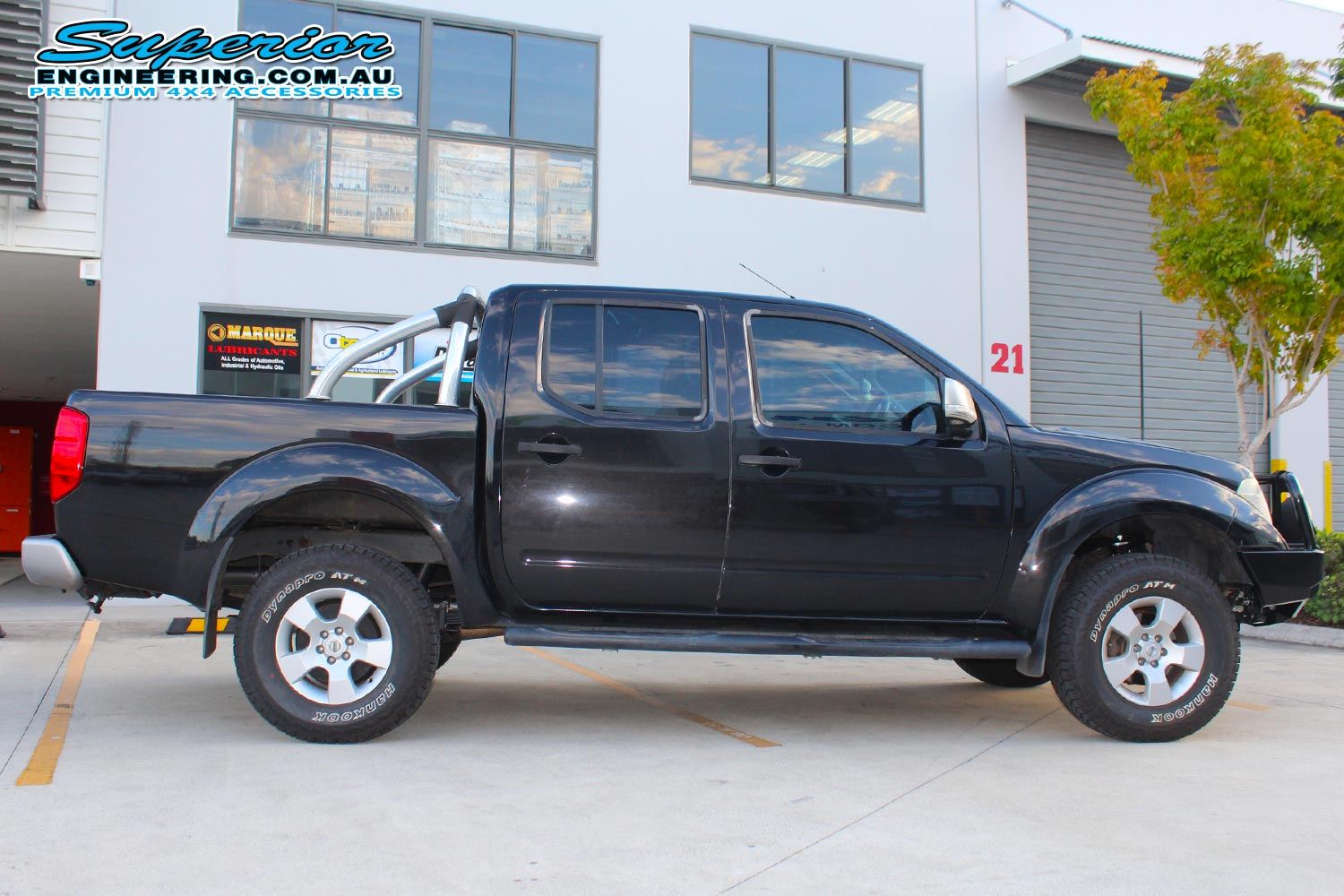 Right side view of a black dual cab Nissan Navara D40 after fitting a 40mm Ironman 4x4 lift kit and some Ironman, Legendex and SuperPro 4x4 accessories