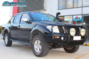 Front right view of a black dual cab Nissan Navara D40 after fitting a 40mm Ironman 4x4 lift kit and some Ironman, Legendex and SuperPro 4x4 accessories