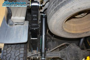 Closeup view of a single Ironman 4x4 leaf spring, shackle and foam cell pro shock fitted to the rear of a Nissan Navara D40 Dual Cab at the Superior 4x4 workshop
