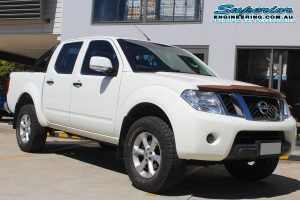 Front right view of a white Nissan Navara D40 dual cab after being fitted with a 2 inch Bilstein lift kit at the Superior Deception Bay 4x4 retail showroom