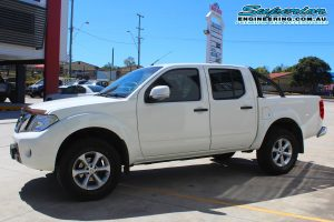 Left side view of a white Nissan Navara D40 dual cab after being fitted with a 2 inch Bilstein lift kit at the Superior Deception Bay 4x4 retail showroom