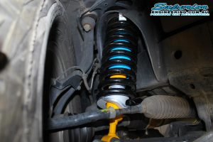 Closeup view of a single EFS coil spring and Bilstein strut fitted to the front of a Nissan Navara D40 (Dual Cab)