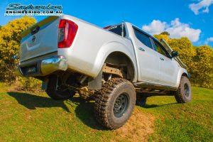 Rear right end view of the silver NP300 Nissan Navara (dual cab) after fitting a big lift kit and then testing out the rear flex on some mounds at Superior Engineering