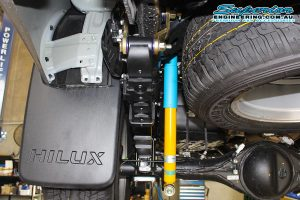Closeup view of a single Bilstein shock, shackle, ubolt and leaf spring fitted to the rear of a current model Toyota Hilux Revo four wheel drive on the hoist at Superior