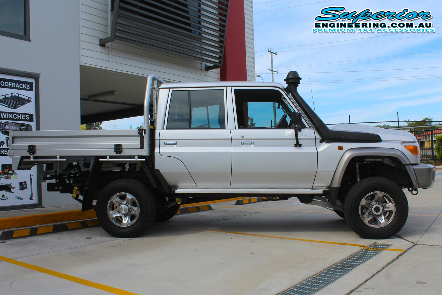 Right side view of a silver dual cab 79 Series Toyota Landcruiser after fitting a Superior Remote Reservoir Superflex Lift Kit