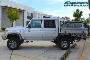 Left side view of the silver dual cab 79 Series Toyota Landcruiser after fitting a Superior Remote Reservoir Superflex Lift Kit