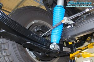 Closeup view of a single Superior shock, high clearance u-bolt plate and leaf spring fitted to the rear of the 79 Series Toyota Landcruiser while on the hoist at Superior