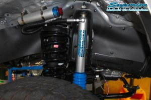 Closeup view of a single Superior remote res shock and coil spring fitted to the front of the 79 Series Toyota Landcruiser while on the hoist at Superior