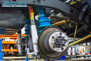 Closeup view of the Superior Engineering Coil Kit showing the shocks, coils, airbags and control arms fitted to the 79 Series Toyota Landcruiser on the hoist at the main Burpengary workshop