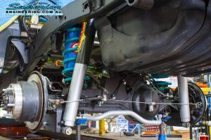 Closeup view of the Superior Engineering Coil Kit showing the shocks, coils, airbags, brackets, mounts and swaybar fitted to the 79 Series Toyota Landcruiser on the hoist at the main Burpengary workshop