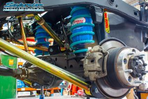 Closeup view of the Superior Engineering Coil Kit showing the shocks, coils, airbags, brackets, mounts and control arms fitted to the 79 Series Toyota Landcruiser on the hoist at the main Burpengary workshop