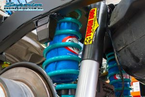 Closeup view of the Superior Engineering Coil Kit showing the shocks, coils and airbags fitted to the 79 Series Toyota Landcruiser on the hoist at the main Burpengary workshop