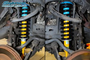 Closeup view of a set of Bilstein struts and black EFS coil springs fitted to the front of a 120 Prado while on the hoist at Superior Engineering