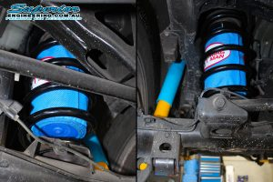 Closeup view of a set of Bilstein shocks, black EFS coil springs and airbags fitted to the rear of a 120 Prado while on the hoist at Superior Engineering