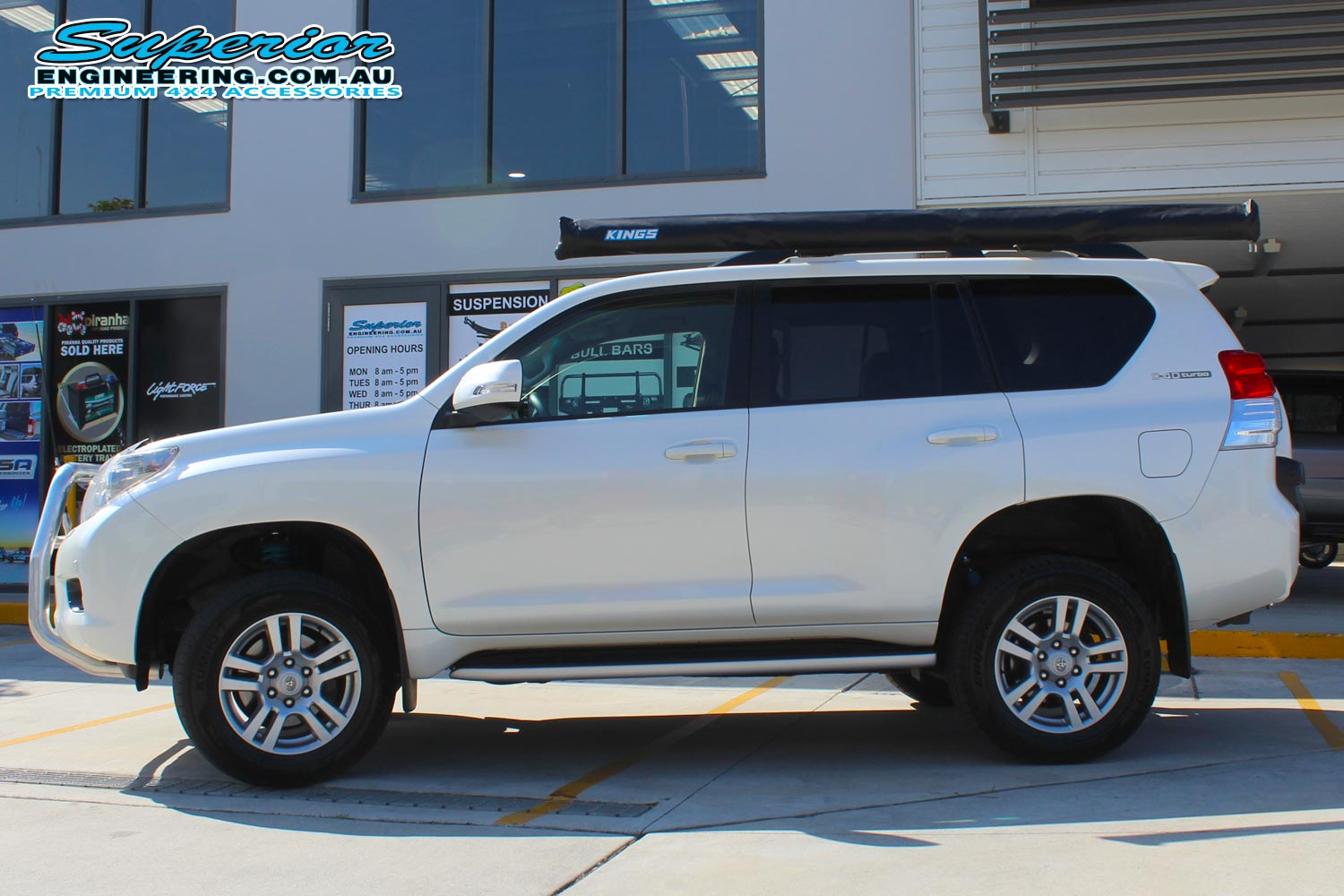 Left side view of a white 150 Prado after fitting the 2 inch Bilstein lift kit at the Superior Engineering 4WD retail showroom
