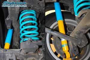 Closeup view of a set of Bilstein shocks and heavy duty dobinson coil springs fitted to the rear of a 150 Prado while on the hoist at Superior Engineering