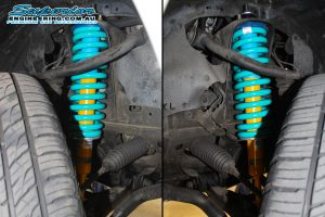 Closeup view of a set of Bilstein struts and heavy duty dobinson coil springs fitted to the front of a 150 Prado while on the hoist at Superior Engineering