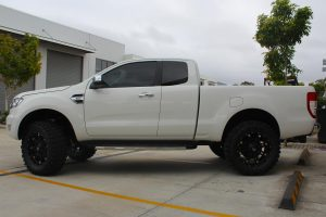 Left side view of a white Ford Ranger fitted with a heavy duty 3 inch Nitro Gas lift kit from Superior Engineering