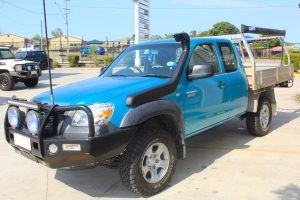 Front right view of a blue extra cab Mazda BT-50 fitted with a premium 35mm Bilstein lift kit and Ironman 4x4 snorkel at the Superior Engineering Deception Bay 4x4 showroom