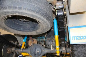 Closeup under vehicle view of a pair of Bilstein shocks, EFS leaf springs and shackles fitted to the rear of the Mazda BT-50 Extra Cab