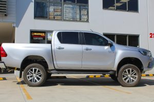 Right side view of a silver Toyota Hilux Revo dual cab fitted with a range of premium four wheel drive suspension components from Superior Engineering