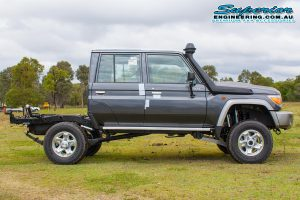 Right side view of a dark grey dual cab 79 Series Toyota Landcruiser after fitting a 4 inch Superior Remote Reservoir Superflex Lift Kit
