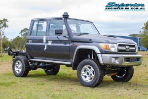 Front right view of a dark grey dual cab 79 Series Toyota Landcruiser after fitting a 4 inch Superior Remote Reservoir Superflex Lift Kit