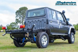 Rear right end view of a V8 79 Series Toyota Landcruiser dual cab after fitting a 4 inch Superior Remote Reservoir Superflex Lift Kit at the main Superior Engineering Burpengary warehouse