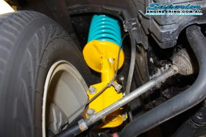 Closeup view of a single Dobinson strut and coil spring fitted to the front of a Suzuki Grand Vitara