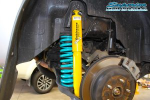 Closeup view of a single Dobinson shock absorber and coil spring fitted to the rear of a Suzuki Grand Vitara on the hoist at Superior Engineering