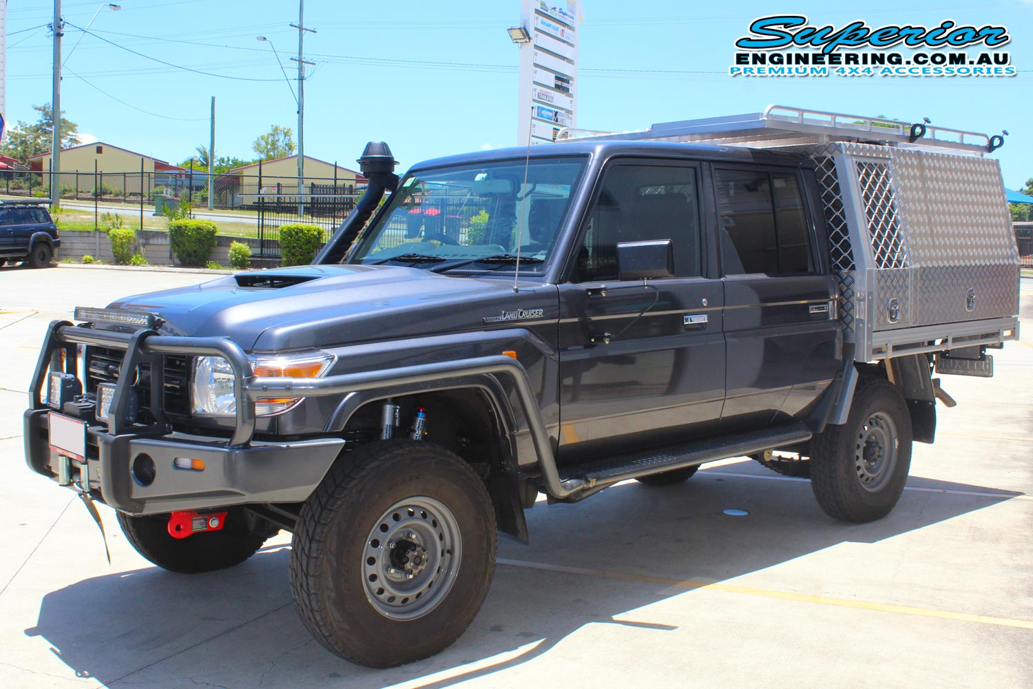Front left view of a grey dual cab 79 Series Toyota Landcruiser after fitting the 2 inch Superior Remote Reservoir lift kit at the Superior Engineering Deception Bay Showroom car park