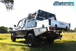 Back left view of a grey dual cab 79 Series Toyota Landcruiser after fitting the 2 inch Superior Nitro Gas Lift Kit + Allied Wheels