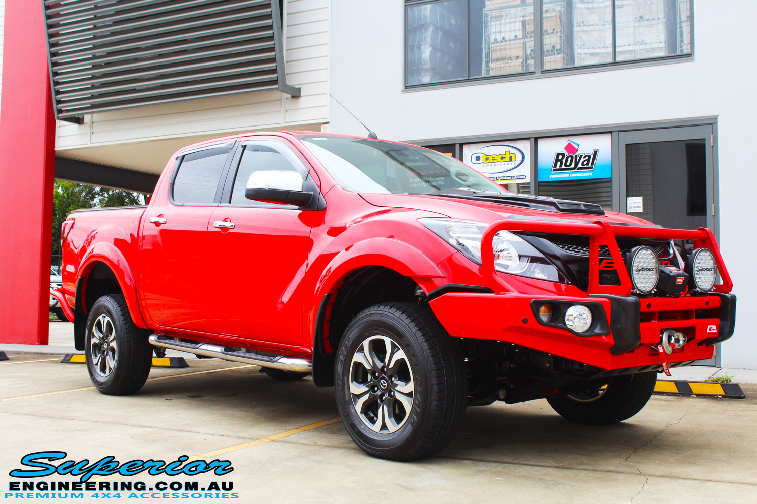 "Right front side view of a Red Mazda BT50 Dual Cab after fitment of a Superior Nitro Gas 2"" Inch Lift Kit, Lightforce Lights, Warn Winch, MCC Bullbar + Heaps of Accessories"