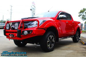 "Left front side view of a Red Mazda BT50 Dual Cab after fitment of a Superior Nitro Gas 2"" Inch Lift Kit, Lightforce Lights, Warn Winch, MCC Bullbar + Heaps of Accessories"