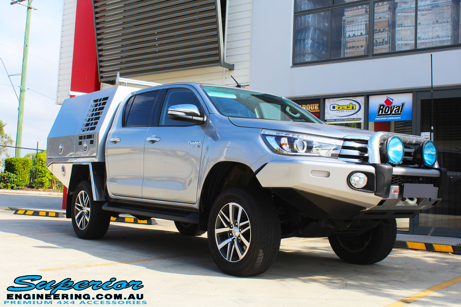 """Right front side view of a Grey Toyota Hilux Revo after fitting a Superior Remote Reservoir 2"""" Inch Lift Kit"""