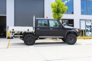 """Right side view of a Black Toyota 79 Series Landcruiser Dual Cab after fitting a Superior Remote Reservoir 2"""" Inch Lift Kit with Airbag Man Leaf Air Kit and Tray"""