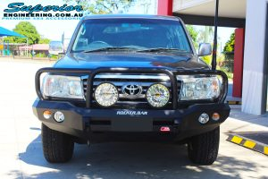 Front view of a Toyota Landcruiser 100 Series after fitment of a MCC Rocker Bullbar, Lightforce DL230 HTX's & GME TX3520s UHF
