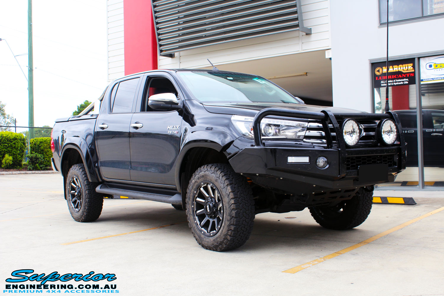 """Right front side view of a Black Toyota Hilux Revo after fitting a 2"""" inch lift with Superior Remote Reservoir Rear Shock & Front Strut and Coil & Leaf Springs"""
